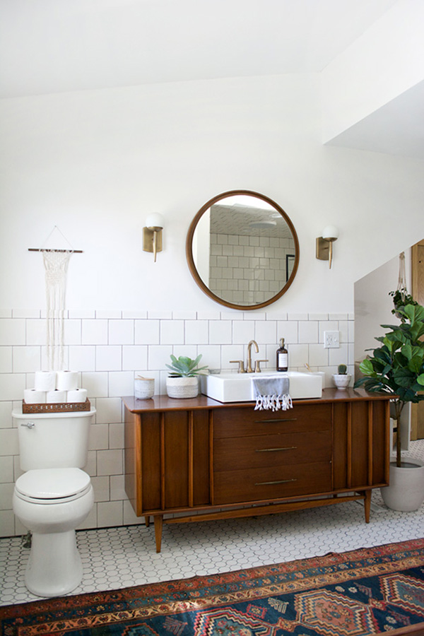 A white and wooden bathroom with a vintage cabinet