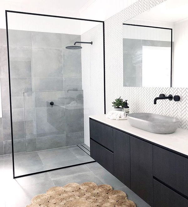 A white bathroom with a screen with black profiles