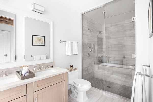 A white bathroom with wooden cabinet