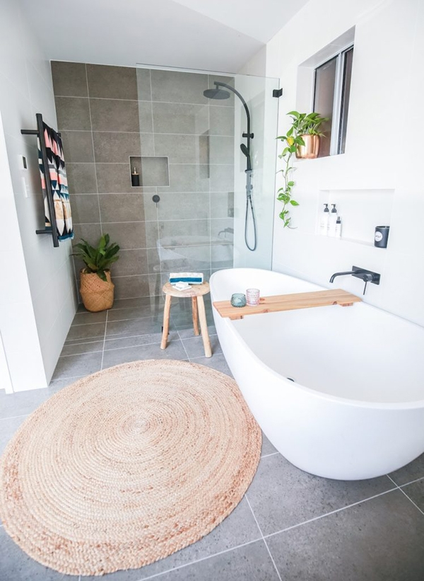 A bathroom in shades of gray and white with touches of wood and a round jute rug