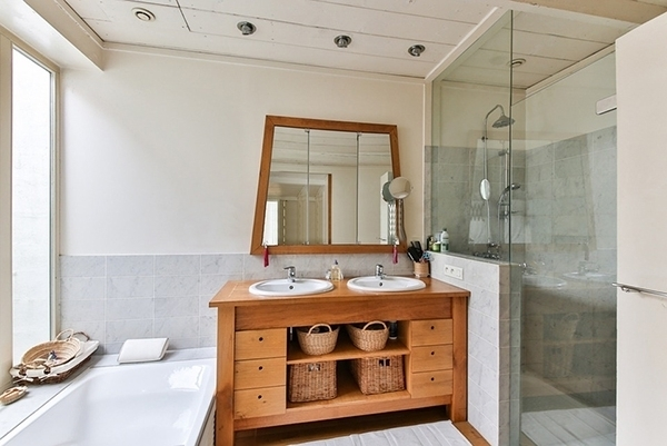 A bathroom in gray tones with beige walls and wooden furniture