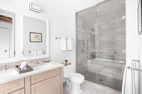 A bathroom in gray and white tones and with natural wood furniture