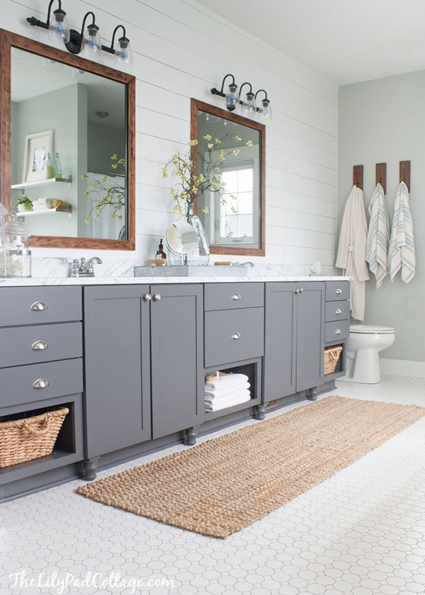 A gray and white bathroom with wood and plant fiber accents