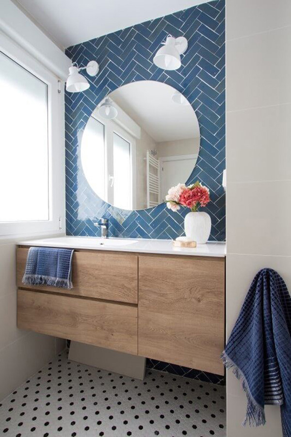 Small bathroom with blue subway tile and round mirror