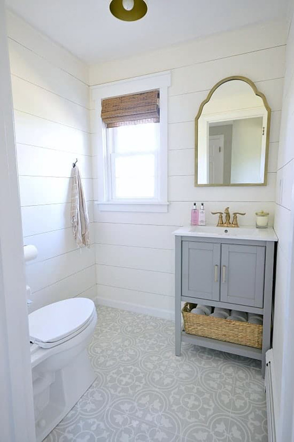 A small bathroom with white painted wood paneled walls