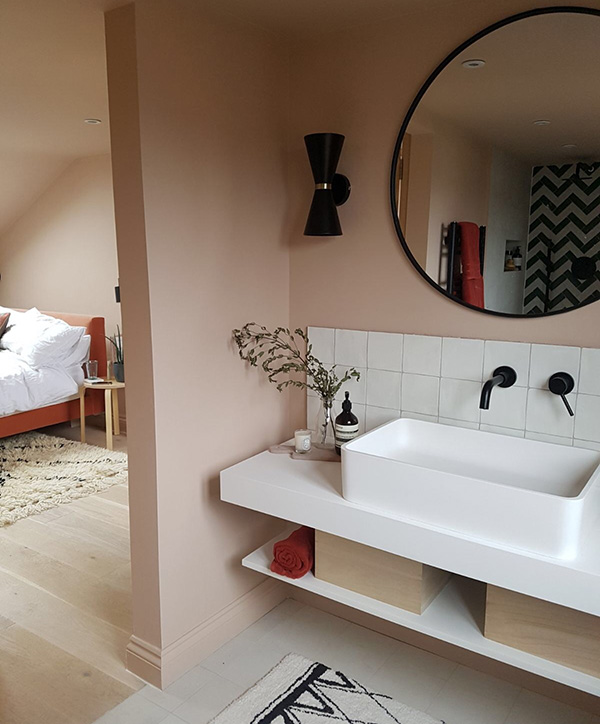 A small bathroom in pink and black