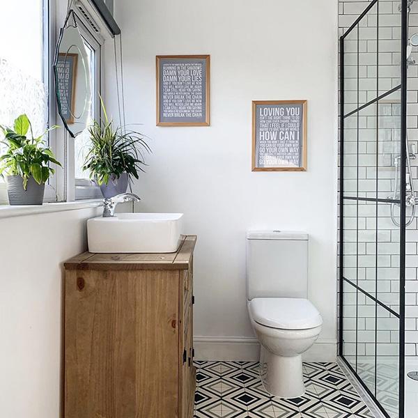 Un cuarto de baño pequeño con una mampara de metal negro con cuarterones de cristal.