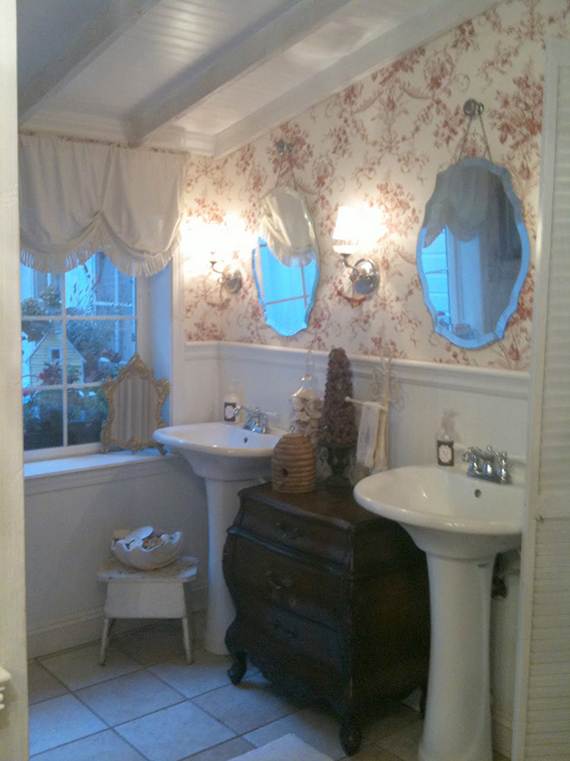 A vintage bathroom with red patterned wallpaper and vintage furniture