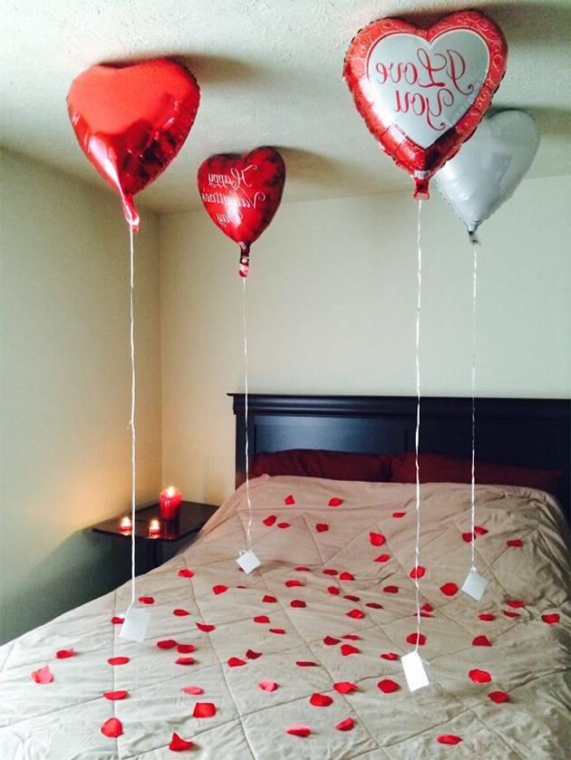 Una cama decorada con pétalos de rosas y globos