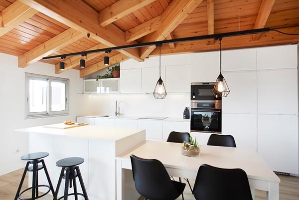 Una cocina blanca con isla, madera y acentos negros