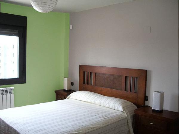 Un dormitorio que combina gris piedra y verde. Colores que combinan con el color piedra.