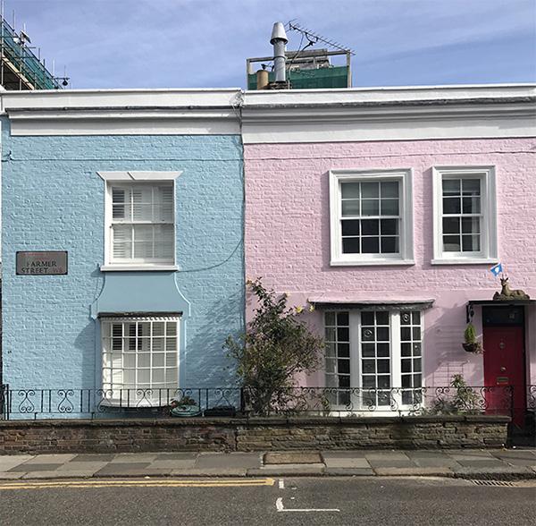 Frente de casa pintado de color azul y rosa
