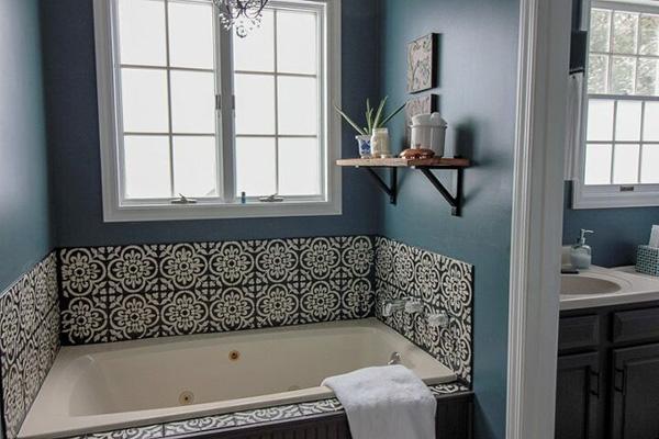Un baño pintado de azul oscuro con azulejos negros y blancos