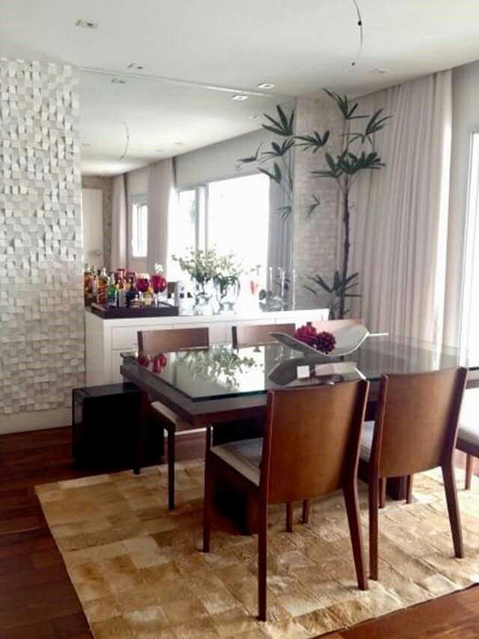 A dining room with a wall decorated with a large mirror and 3D cladding