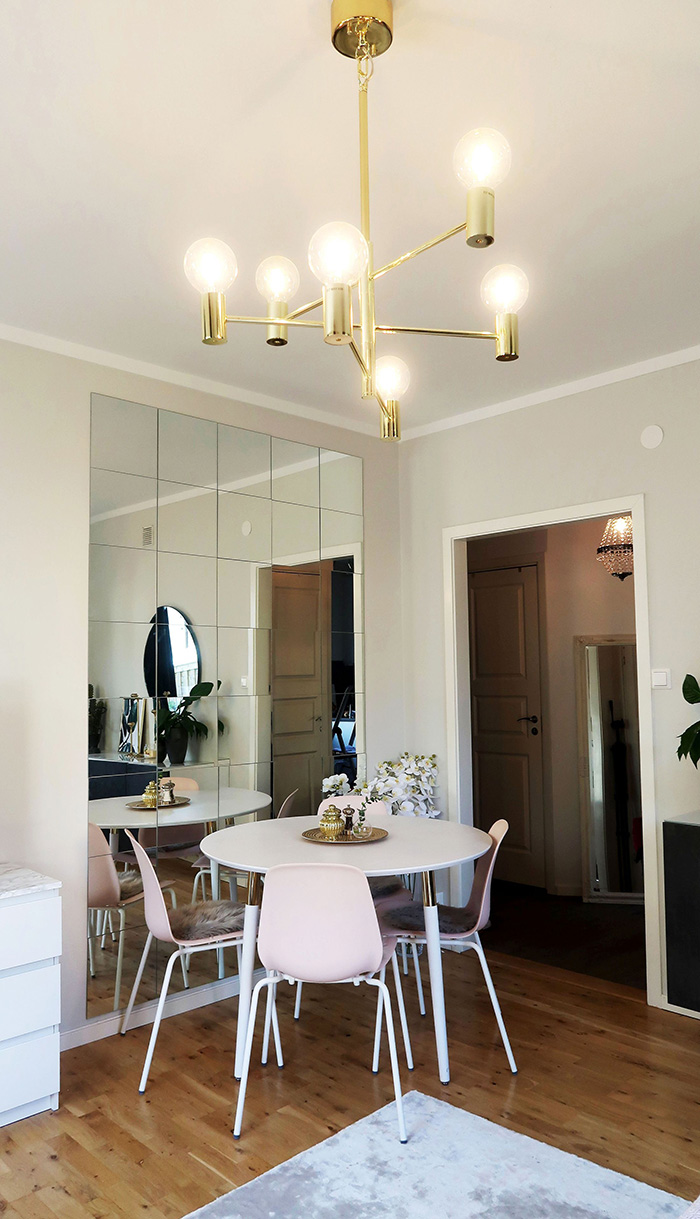 A dining room decorated with a beveled mirror wall
