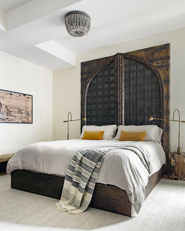 Un dormitorio con un cabecero hecho de puertas antiguas