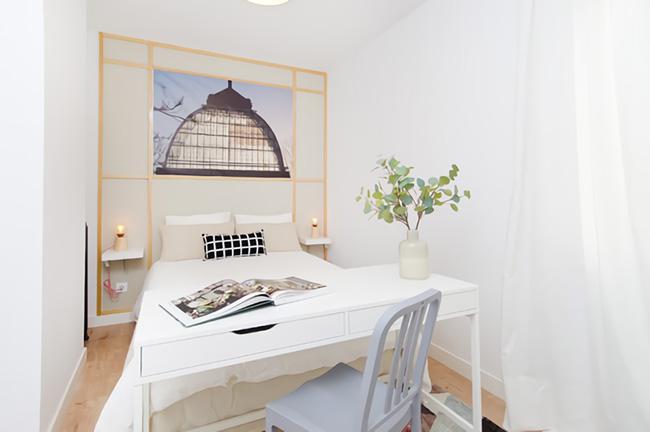 Un dormitorio pequeño con una estructura de listones de madera en el cabecero y un escritorio en elos pies