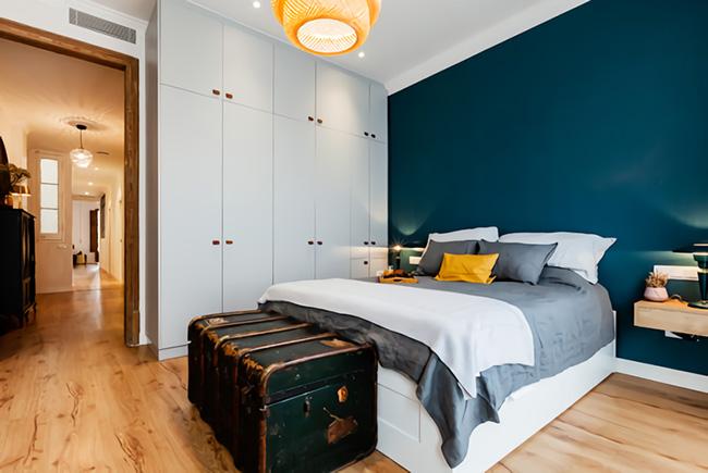 Un dormitorio decorado en azul oscuro con un baúl vintage como pie de cama