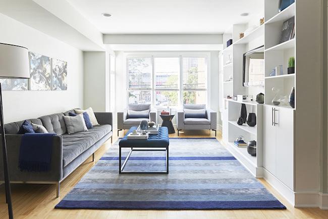 Un amplio salón rectangular luminoso en tonos grises y azules
