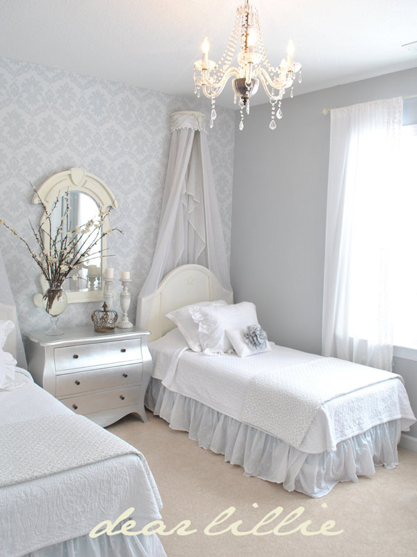 Una habitación compartida con dos camas con cielo de cama y papel pintado en la pared