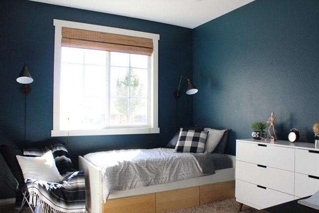 Un dormitorio o cuarto para un chico adolescente pintado en azul oscuro