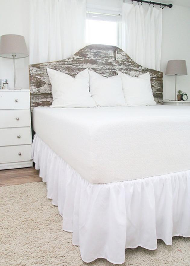 Un dormitorio vintage moderno con cabecero de madera desgastada