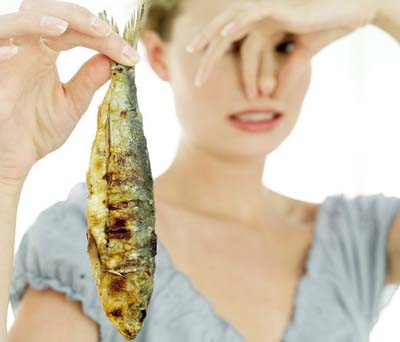 Close-up of woman holding a fried fish and holding her nose
