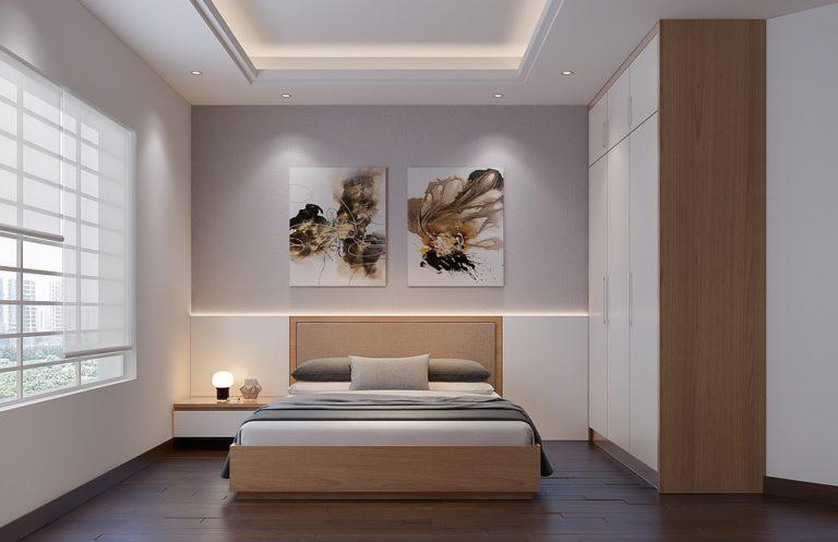 Un dormitorio con muebles de madera clara pintado de gris y blanco