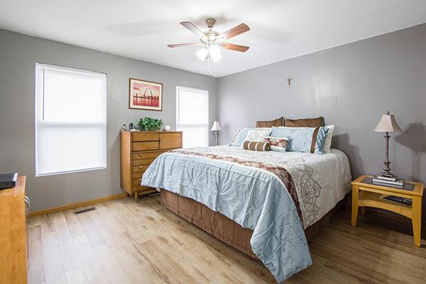 Un dormitorio con muebles de madera clara pintado de gris