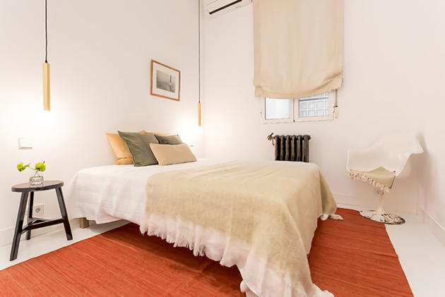 Una habitación pequeña en blanco con una alfombra roja