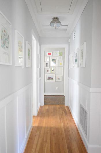 Un pasillo largo y estrecho decorado en gris con un zócalo blanco