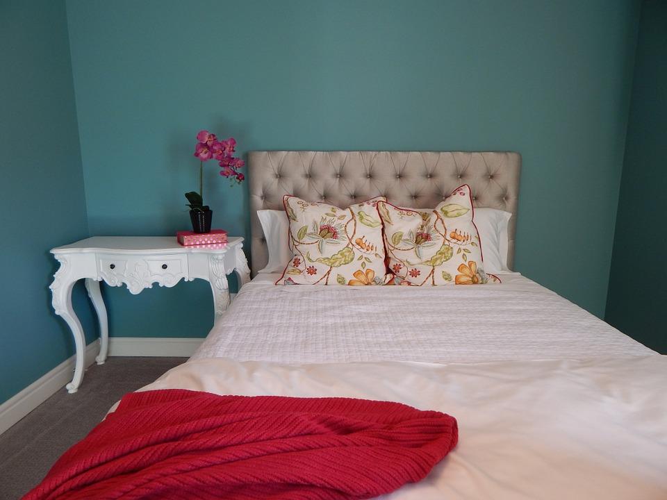 Un dormitorio pintado en turquesa oscuro