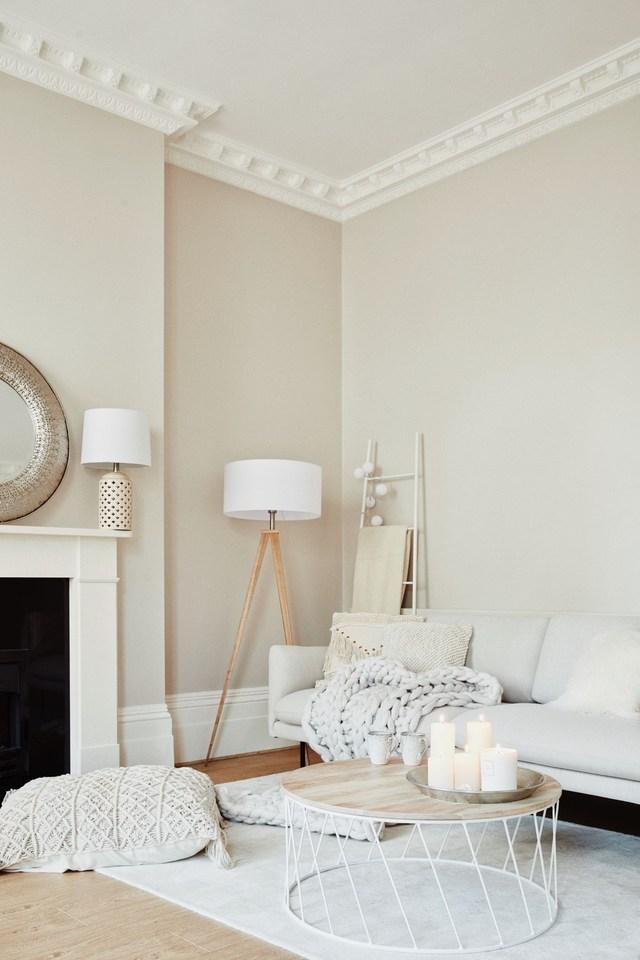 Un salón pintado de beige con muebles blancos