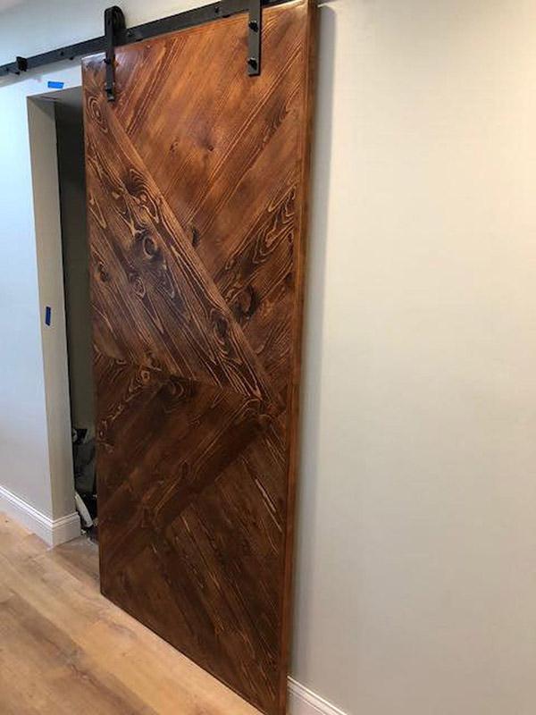 Puerta corredera de granero en madera con herrajes de metal en negro